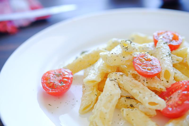 Pasta with cream sauce, cheese, sour cream, tomatoes, herbs and spices, on a white plate on a wooden table, close-up. Italian royalty free stock photo