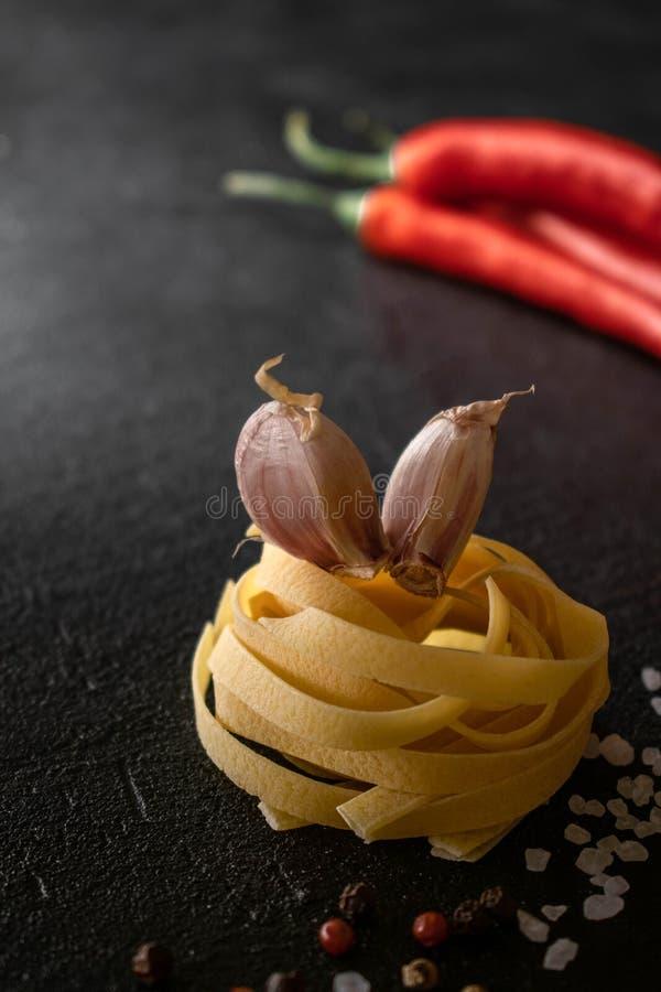 Pasta cruda del fettuccine con i chiodi di garofano di aglio, il forno del peperoncino rosso e le spezie immagine stock libera da diritti