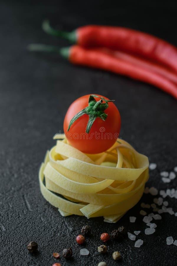 Pasta cruda del fettuccine con il sale marino ed i granelli di pepe grezzi del peperoncino rosso del pomodoro fotografia stock