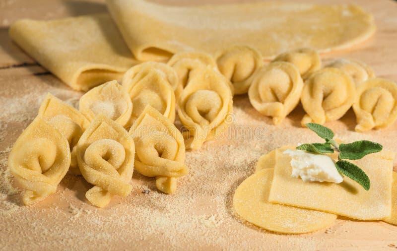 Pasta cruda e tortellini casalinghi italiani, aperto e chiuso, riempiti di formaggio di ricotta e di erbe aromatiche immagini stock