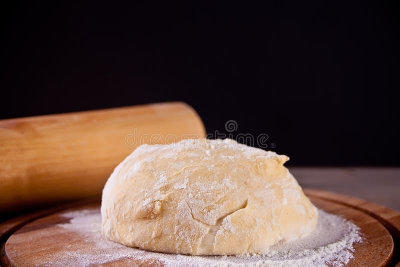 Pasta cruda fresca para la hornada de la pizza o del pan en tabla de cortar de madera en fondo negro foto de archivo libre de regalías