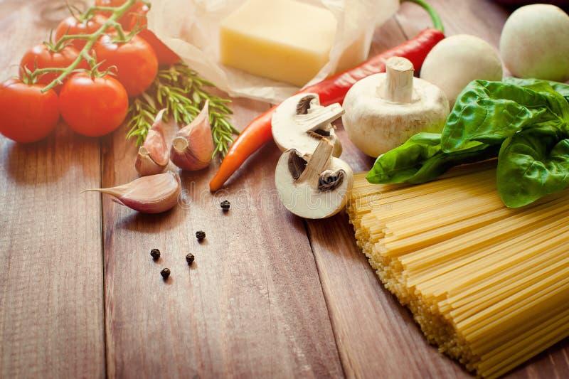 Pasta cruda, pomodori, funghi ed altri prodotti sul fondo di legno della tavola, vista superiore fotografia stock