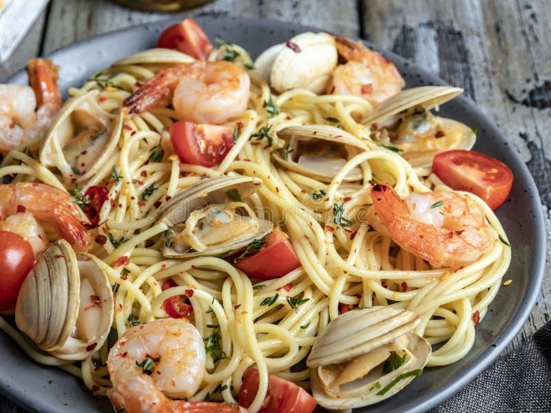 Pasta cucinata con le vongole dei frutti di mare, pomodoro su un piatto, spaghetti dei gamberetti immagine stock