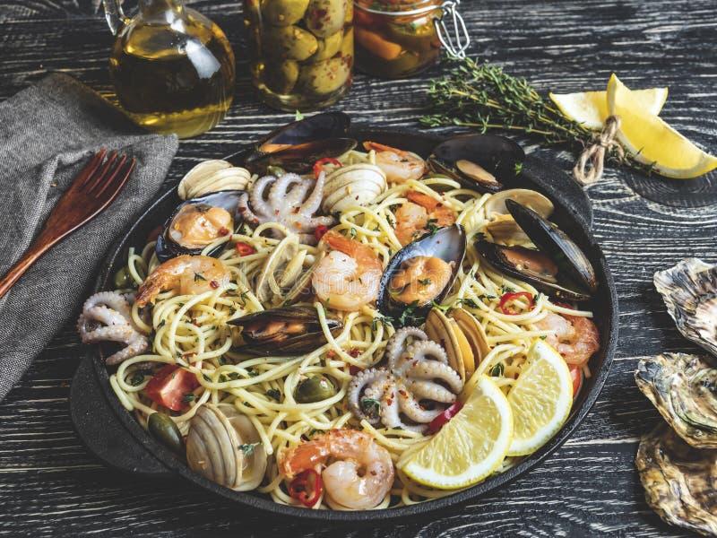 Pasta cucinata con le vongole, gamberetti, polipo del bambino, pomodoro su una padella, spaghetti delle cozze fotografia stock libera da diritti