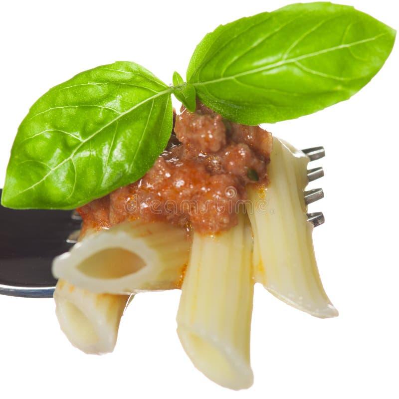 Pasta cucinata fresca sulla forcella con salsa bolognese e basilico verde fotografia stock