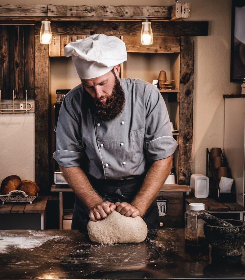 Pasta d'impastamento concentrata del cuoco unico nella cucina fotografie stock