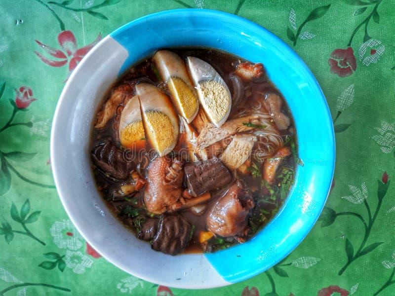 A pasta da farinha de arroz com ovos cozidos, adiciona a carne de porco, a galinha cozido, os vegetais, a sopa do osso da carne d foto de stock royalty free