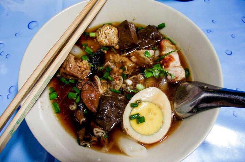 Pasta da farinha de arroz, feita sob a forma das folhas, do corte acima, posta em uma sopa, e coberta com fatias de galinha e de  imagem de stock
