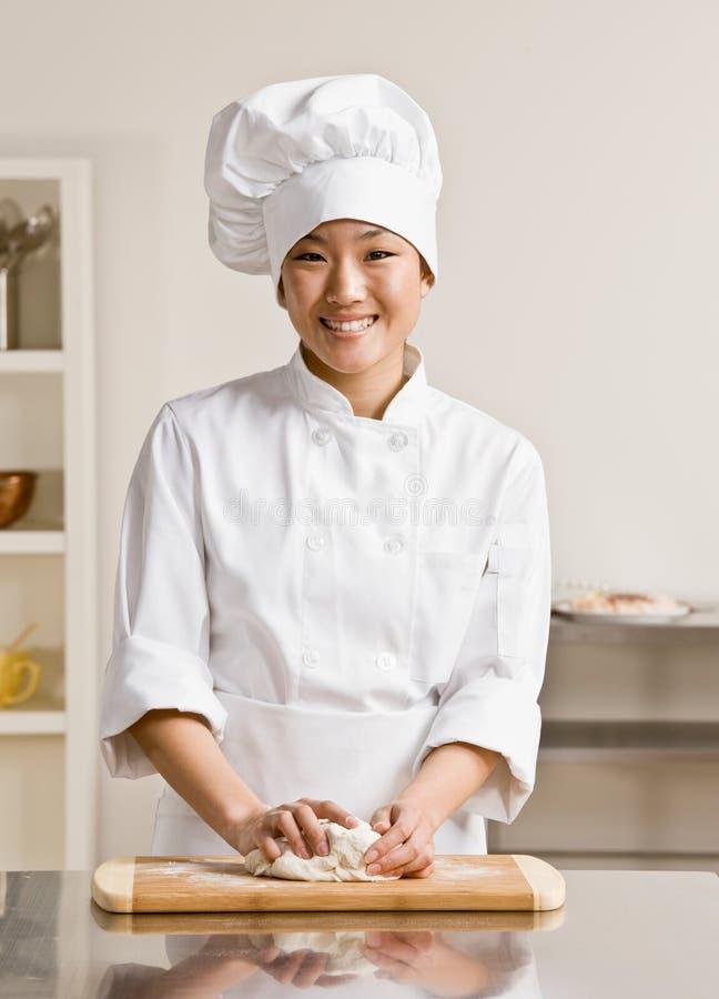 Pasta de amasamiento del cocinero en cocina comercial imagen de archivo libre de regalías