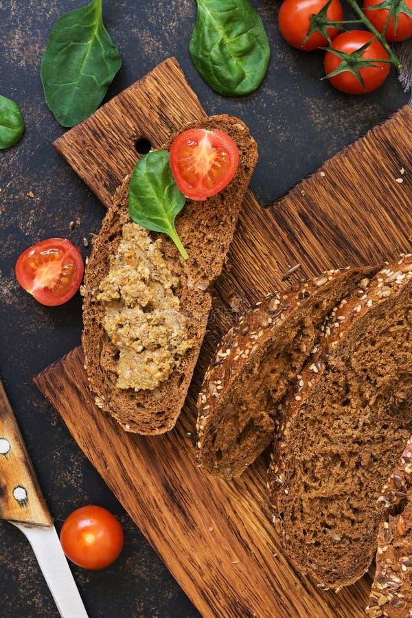 Pasta de fígado caseiro no pão da grão do centeio, nos tomates de cereja e nas folhas dos espinafres em uma placa de corte Vista  foto de stock royalty free
