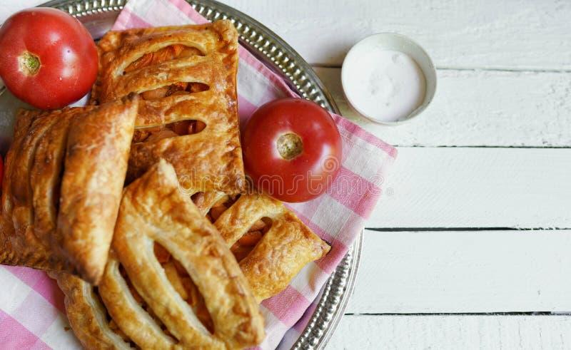 Pasta de hojaldre con el tomate en una tabla de madera blanca con el espacio de la copia imagenes de archivo