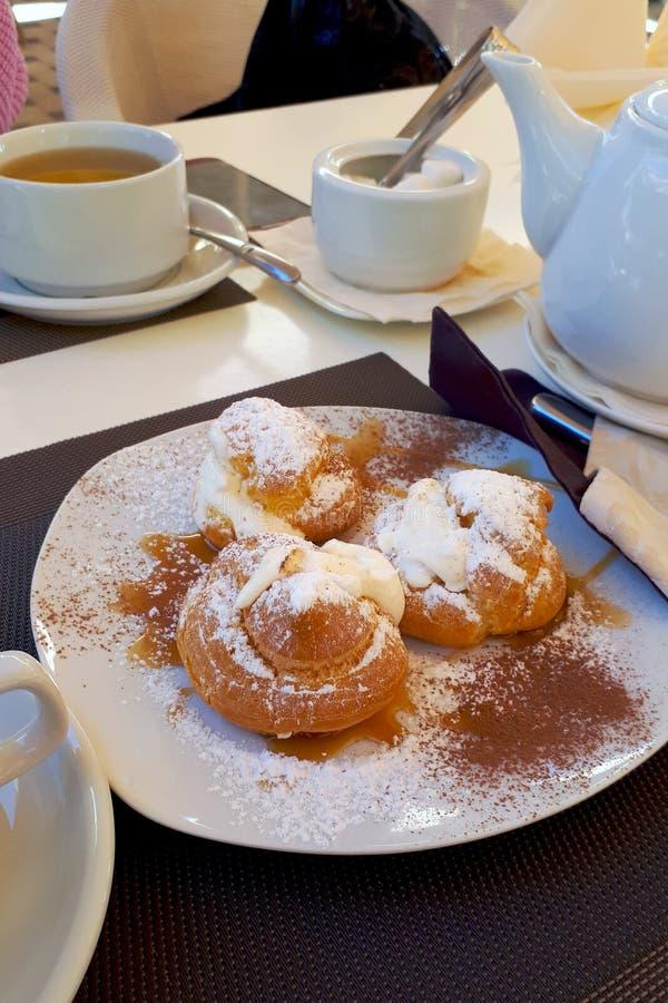 Pasta de hojaldre, fresco dulce y cubierto con el azúcar en polvo en una tabla gris al lado de la caldera y las tazas para el té fotos de archivo