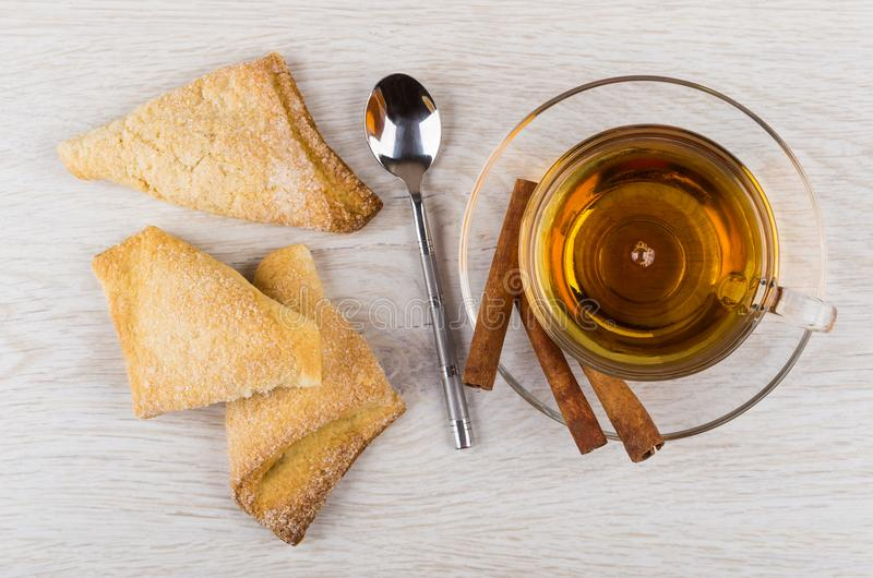 Pasta de hojaldre, taza del té, palillos de canela en el platillo, cuchara imagenes de archivo