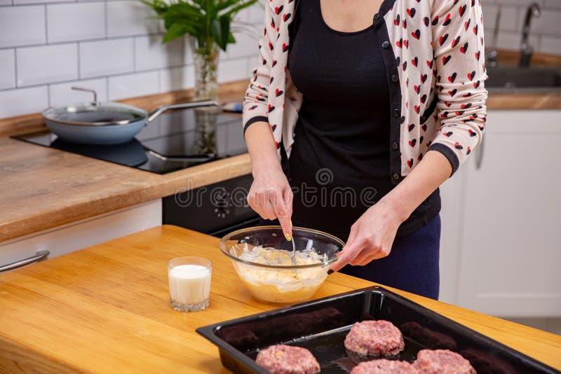 Pasta de mezcla del queso de la mujer joven con una cuchara en cocina fotografía de archivo libre de regalías