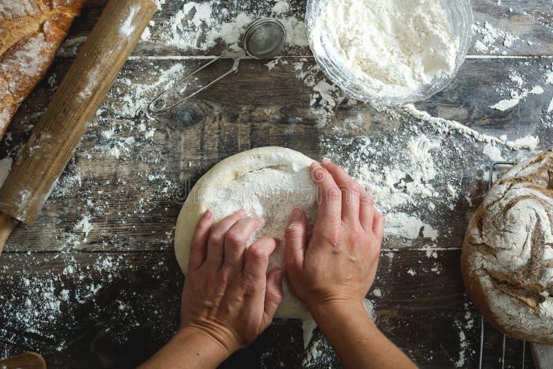 Pasta de pan de amasamiento de la mujer con sus manos fotografía de archivo