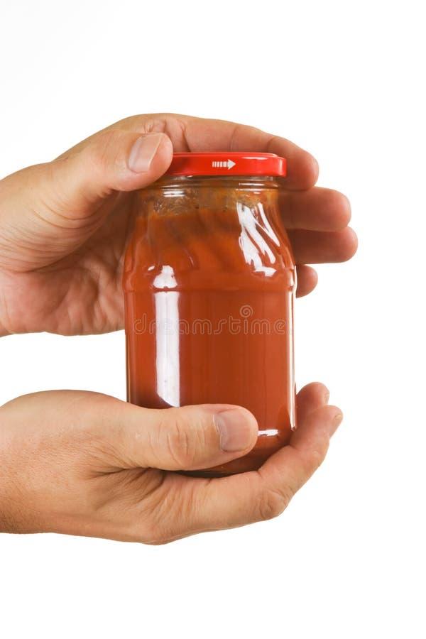 Pasta de tomate do frasco nas mãos imagens de stock royalty free