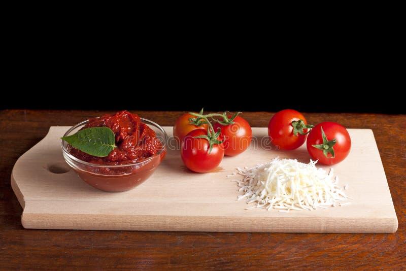Pasta de tomate, queijo e alguns tomates foto de stock