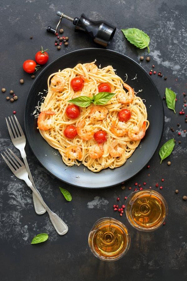 Pasta degli spaghetti con i gamberetti ed il vino bianco su un fondo di pietra scuro Vista superiore fotografie stock libere da diritti