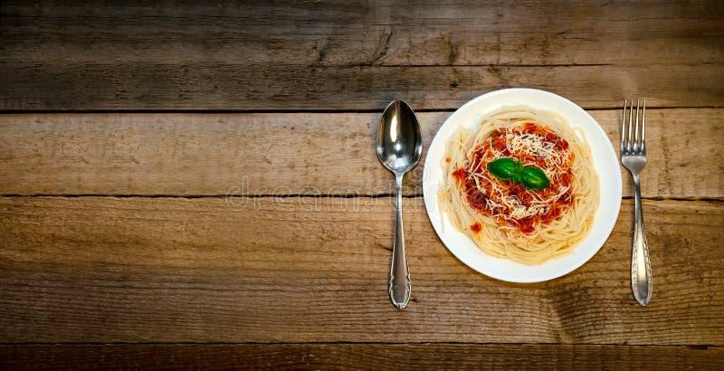 Pasta degli spaghetti con salsa al pomodoro, formaggio e basilico sulla Tabella di legno Alimento italiano tradizionale immagine stock libera da diritti