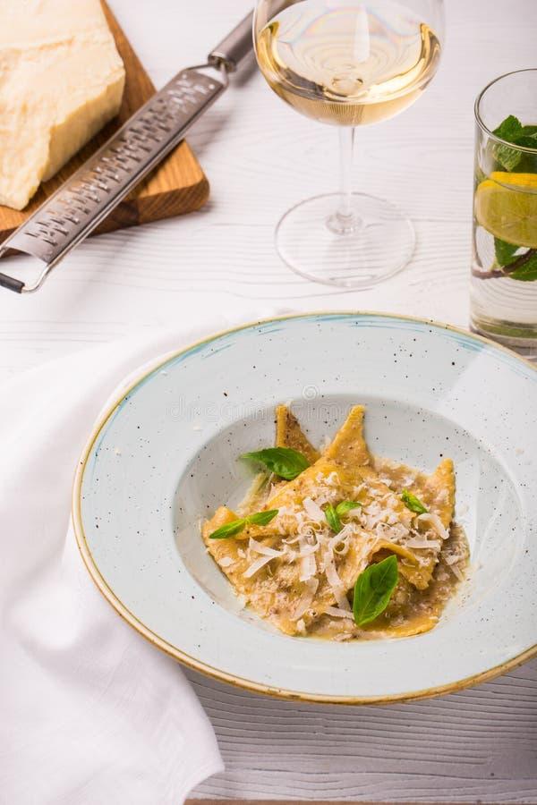 Pasta dei ravioli con basilico e parmigiano sul piatto Parmigiano con una grattugia su un tagliere Foto verticale immagini stock