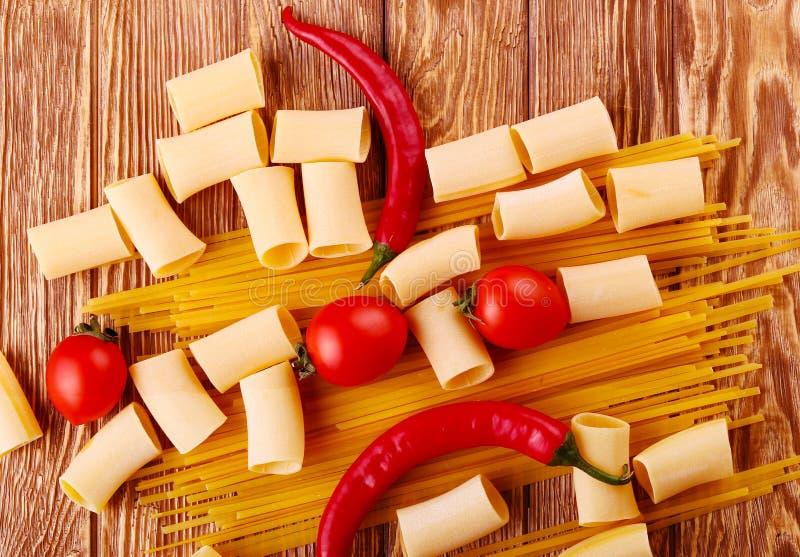 Pasta del collage con i pomodori ciliegia ed altri ingredienti sul fondo di legno della tavola immagine stock