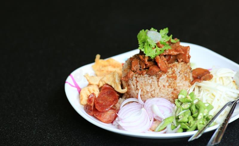 Pasta del gamberetto del riso fritto con carne di maiale e l'uovo fritto in piatto sulla tavola nera Alimento tailandese Kao Cluk fotografia stock libera da diritti