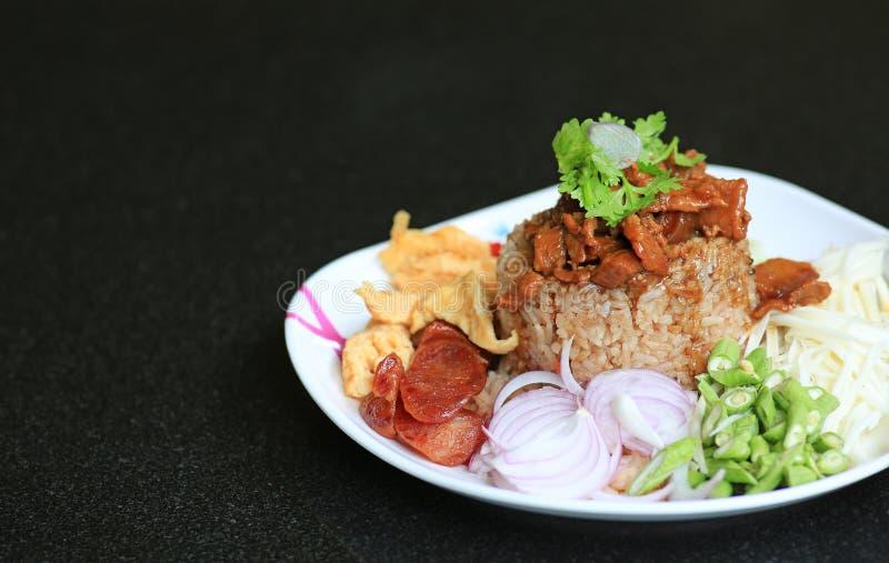 Pasta del gamberetto del riso fritto con carne di maiale e l'uovo fritto in piatto sulla tavola nera Alimento tailandese Kao Cluk immagine stock libera da diritti