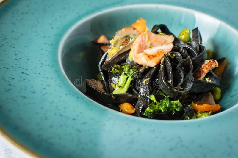 Pasta del nero dell'inchiostro della seppia con il salmone e le verdure fotografie stock libere da diritti