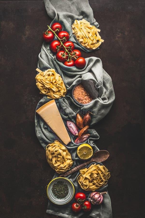 Pasta del tonno che cucina gli ingredienti su fondo rustico scuro, vista superiore Prodotti della drogheria di cucina italiana Al immagine stock libera da diritti