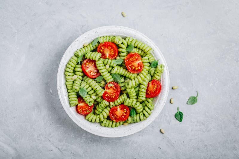 Pasta di Fusilli con la salsa, i pomodori ed i pinoli di pesto del basilico immagini stock