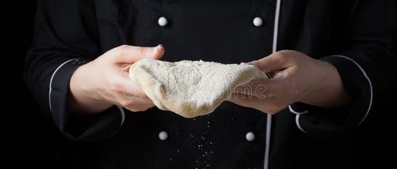 Pasta di lievito femminile della tenuta del cuoco unico in sue mani su fondo nero fotografia stock