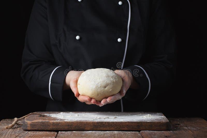 Pasta di lievito femminile della tenuta del cuoco unico in sue mani su fondo nero fotografie stock