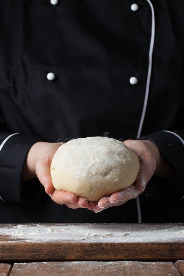 Pasta di lievito femminile della tenuta del cuoco unico in sue mani su fondo nero immagini stock libere da diritti
