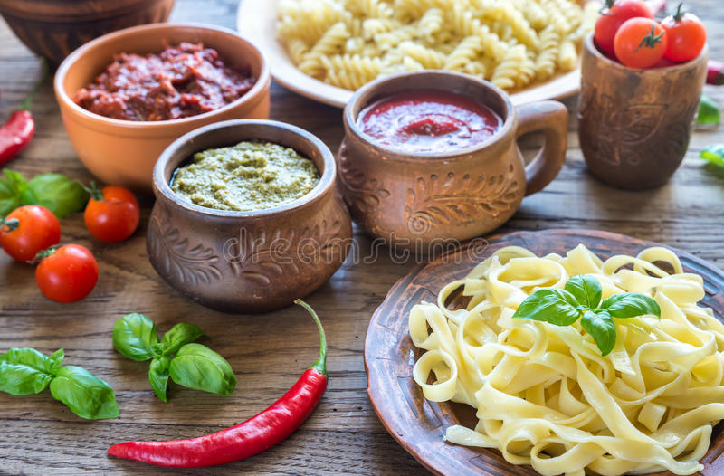 Pasta with different kinds of sauce on the wooden background. Various pasta with different kinds of sauce on the wooden background stock image