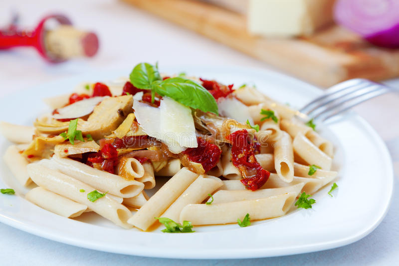 Pasta dish. Closeup image of a pasta dish with sundried tomatoes and caramelized onions royalty free stock images