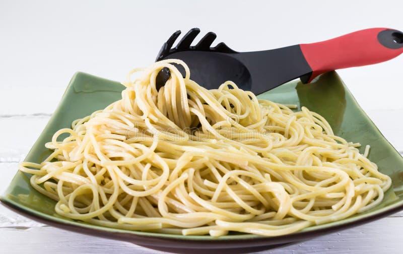 Pasta för Aldentespagetti på en platta med pastagaffeln på vitbac royaltyfri bild