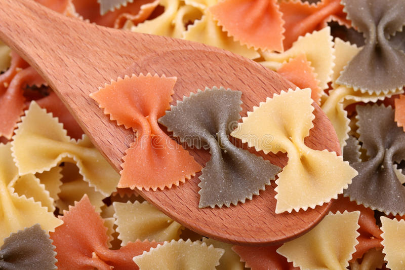 Pasta farfalle tricolore in a wooden spoon stock photo