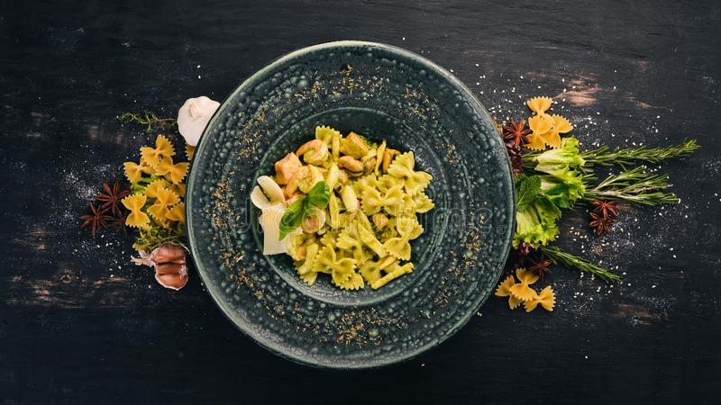 Pasta Farfelli with spinach and seafood. Italian cuisine. Top view. On a black wooden background. Copy space royalty free stock photography