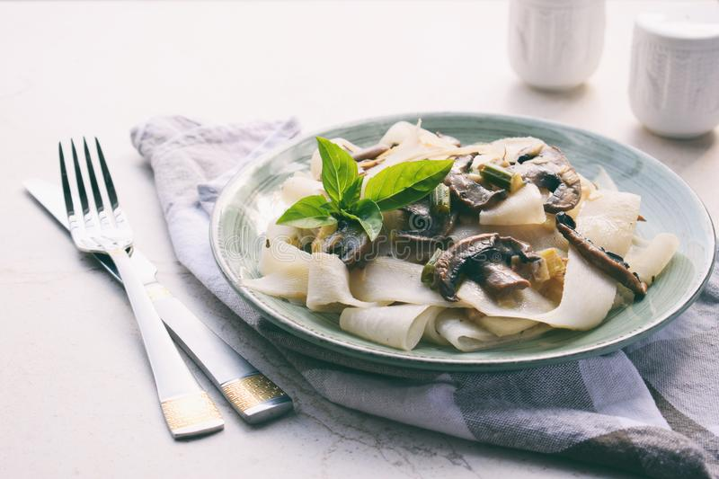Pasta fetuchini from radish radish with mushrooms and basil. Italian AIP breakfast, dinner or lunch. Autoimmune Paleo. Diet. Healthy food concept. Cereals stock image