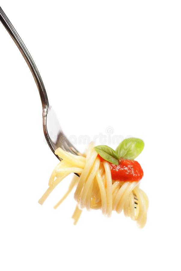 Pasta on a fork. Cleanly isolated pasta swirled onto a fork with sauce and basil leaves stock images