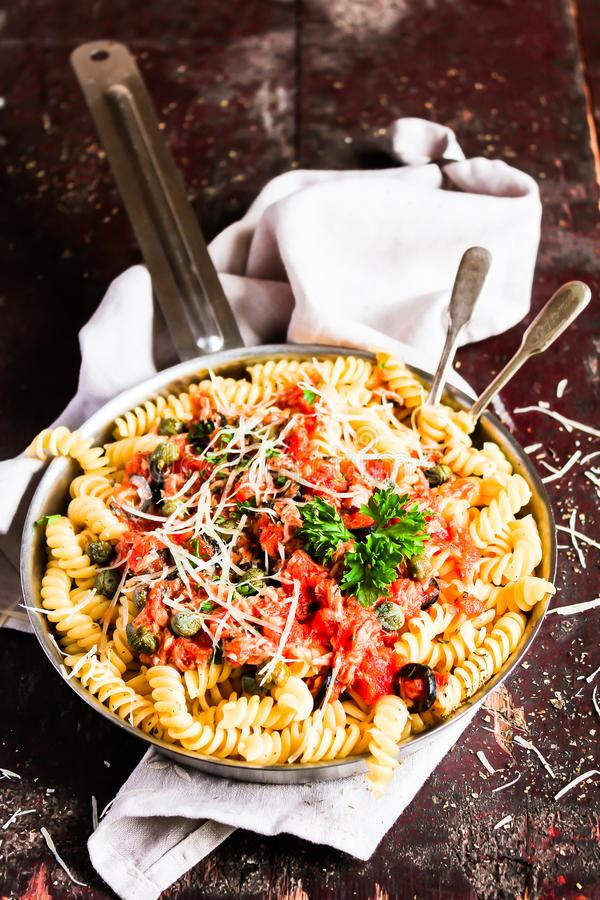 Pasta fusilli meal with canned tuna fish, tomato sauce, black olives, grated cheese and parsley in a cooking pan pn a wooden table royalty free stock images