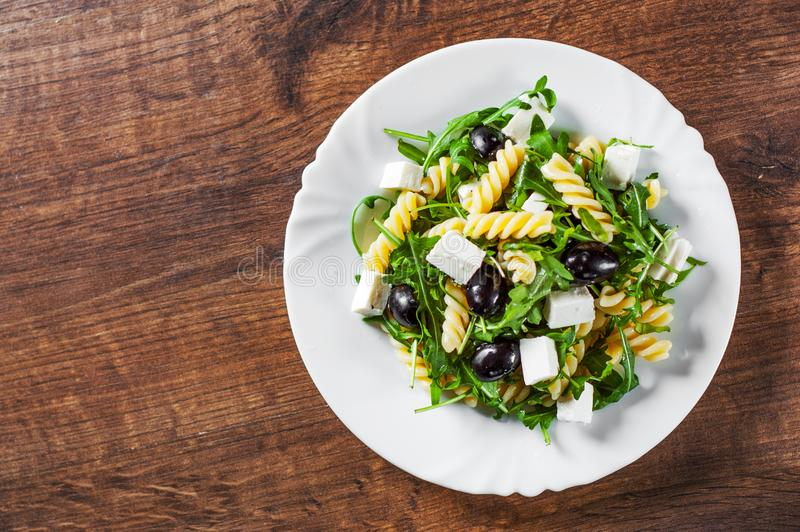 Pasta fusilli salad with arugula, cheese and olive in white plate. On a wooden background royalty free stock images
