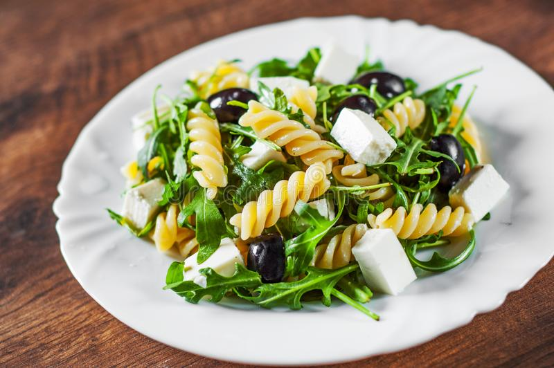 Pasta fusilli salad with arugula, cheese and olive in white plate. On a wooden background stock photography