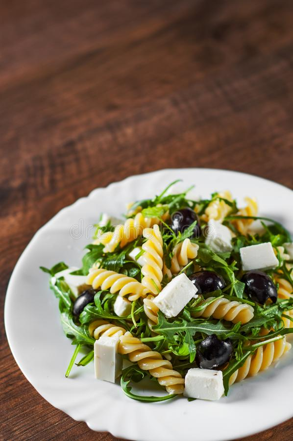 Pasta fusilli salad with arugula, cheese and olive in white plate. On a wooden background stock image
