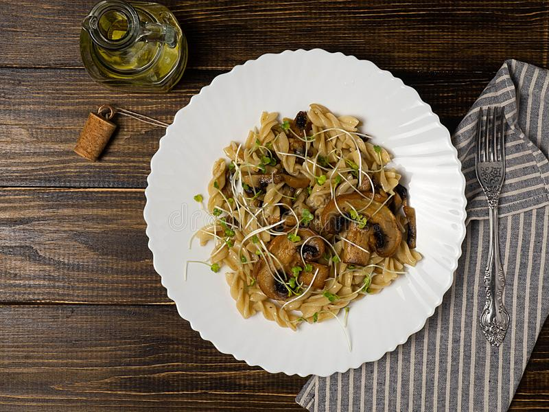 Pasta fusilli wholemeal with mushrooms mushrooms on a dark wooden background, top view. Vegetarian food. royalty free stock photography