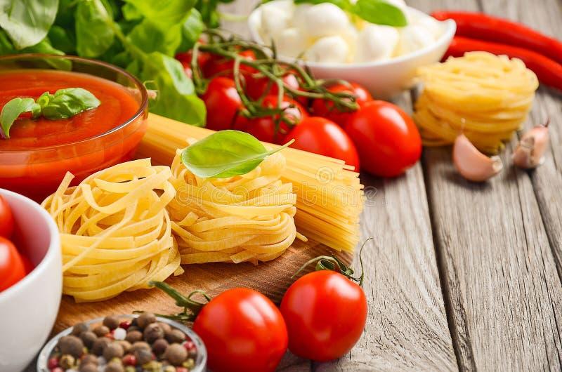 Pasta, grönsaker, örter och kryddor för italiensk mat på den lantliga trätabellen fotografering för bildbyråer