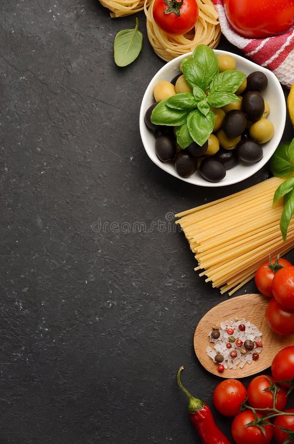 Pasta, grönsaker, örter och kryddor för italiensk mat på svart bakgrund royaltyfria foton