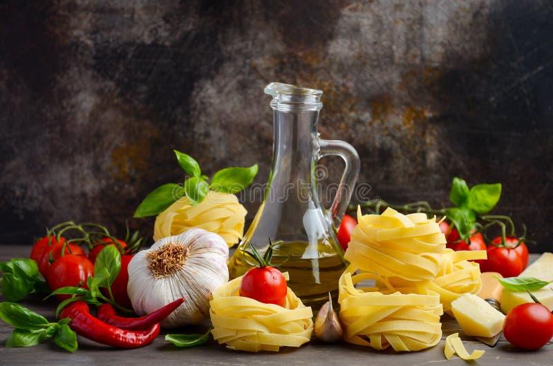 Pasta, grönsaker, örter och kryddor för italiensk mat på träbakgrunden arkivbild