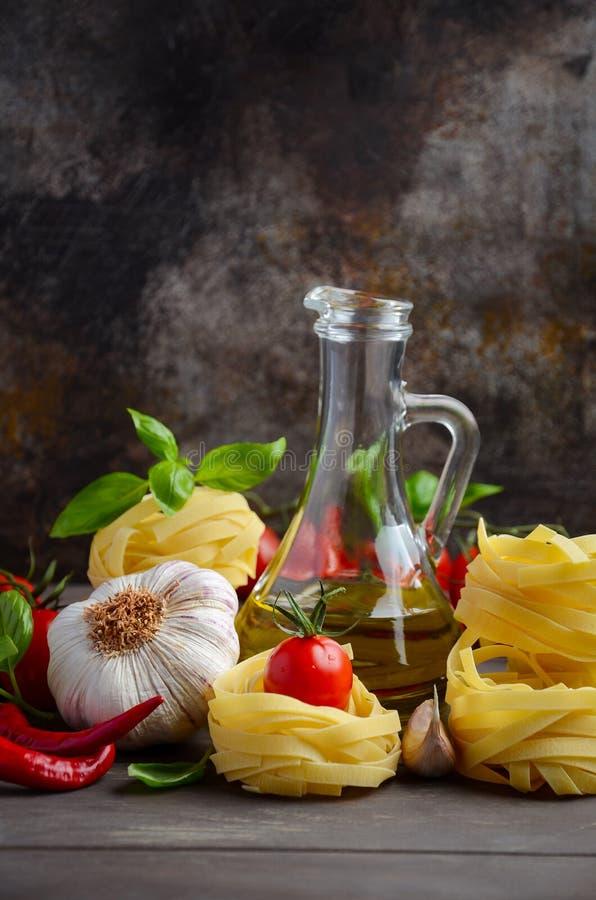 Pasta, grönsaker, örter och kryddor för italiensk mat på träbakgrunden arkivfoto