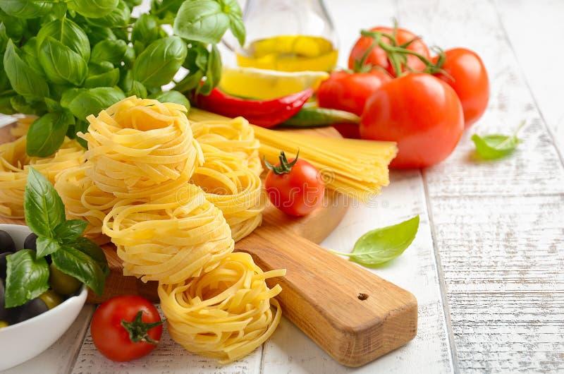 Pasta, grönsaker, örter och kryddor för italiensk mat på vit träbakgrund royaltyfri fotografi